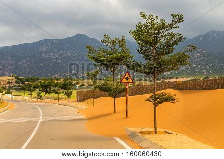An empty raod in vietnam with sand built up on it and mountains in the background