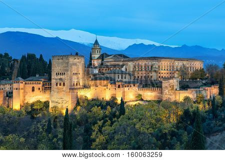 Alhambra - medieval Moorish fortress surrounded by yellow autumn trees illuminated in the evening Granada Andalusia Spain