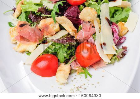 Salad with prosciutto, parmigiano, fresh cherry tomato, lettuce and ruccola, served at white plate