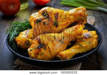 Roasted chicken drumsticks in frying pan close up view