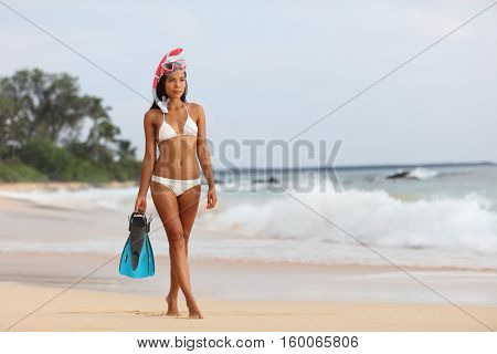 Beach vacation snorkeling woman with scuba diving mask and fins. Sexy bikini Asian snorkeler relaxing after snorkelling activity on summer travel holiday. Snorkel watersport girl walking out of ocean.