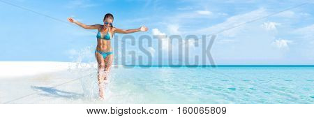 Sexy bikini body woman playful on paradise tropical beach having fun playing splashing water in freedom with open arms. Beautiful fit body girl on travel vacation. Banner crop for copy space.