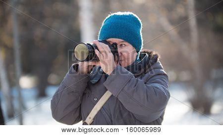 Senior woman with photo camera at sunny winter day, outdoor, horizontal