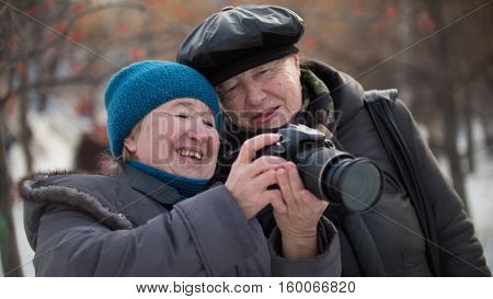 Two senior woman looking to they self photo camera and smiling at winter day, outdoor, outdoor, horizontal