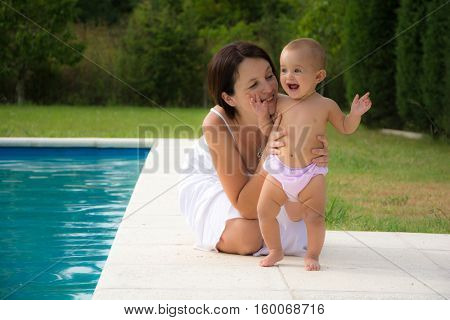 mother with a cute baby sitting by the poo