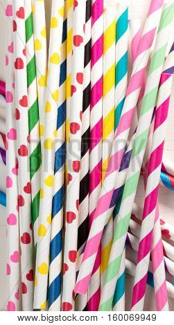 colored straws in a pile on a white wooden table