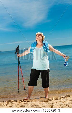 Senior Woman Practicing Nordic Walking On Beach