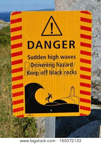 Warning sign of the dangers on the black rocks near the famous lighthouse at Peggy's Cove in Nova Scotia