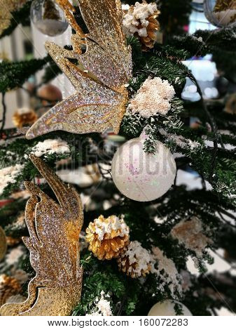 Christmas tree decoration ornaments white glitter ball and gold butterfly with blur boken snow and xmas tree background
