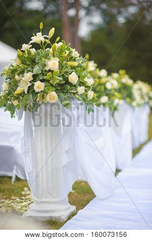 wedding ceremony decoration with white rose. Beautiful wedding flower arrangement of seats along the aisle