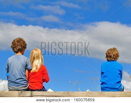 Three kids sitting over the blue sky