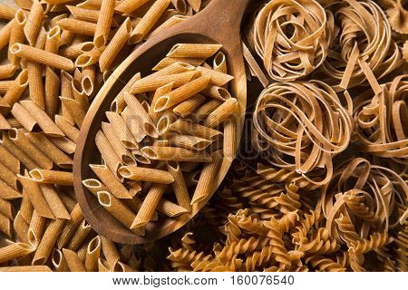 Wholemeal Penne Into A Spoon. Integral Pasta Over A Wooden Table
