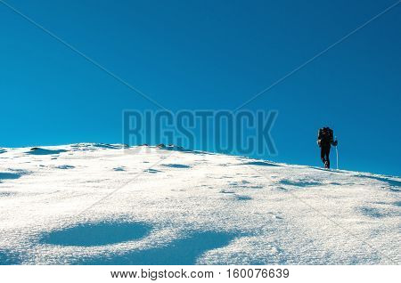 Hiker climbs to the top of Chatyr Dag mountain in the Crimean mountains. Graphically image with clear deep blue sky and white showy slope.