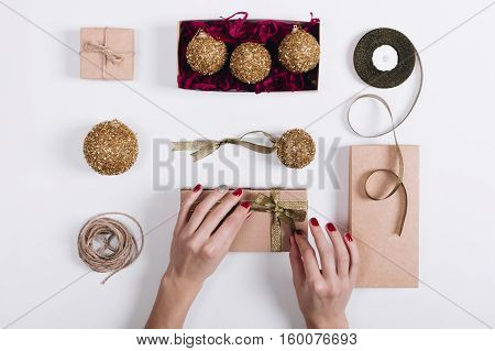 Female Hands With A Red Manicure Tied Ribbon On The Box With A Gift
