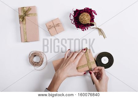 Women's Hands With A Red Manicure Tied Ribbon On The Box With A Gift