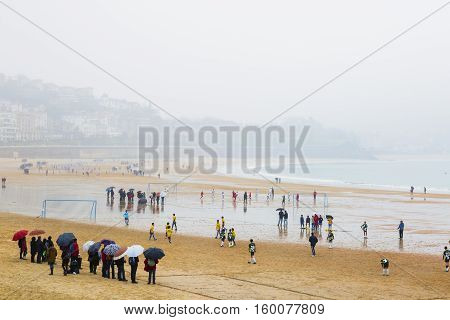 San SebastianSpain - November 26 2016: children playing Football raining in the Concha beach of San Sebastian Spain
