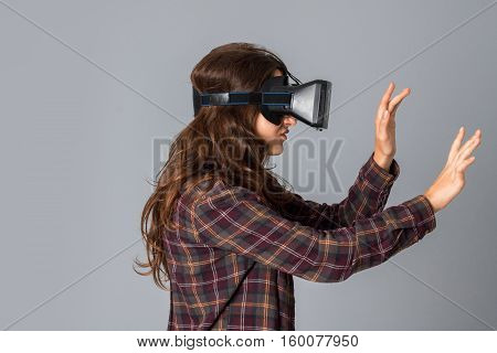 portrait of cutie woman testing virtual reality helmet in studio on grey background