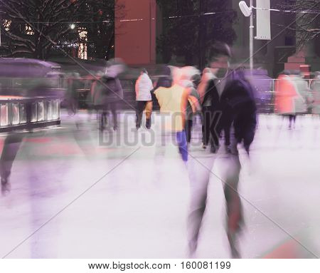 Young man on skates against the backdrop of city skating rink in the park. Image blurring and double composition. Christmas, sport and healthy lifestyle, fun in wintertime.