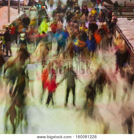Blurred photo of many persons skating on the ice rink in evening time outdoors in the park on winter. Christmas, sport and healthy lifestyle