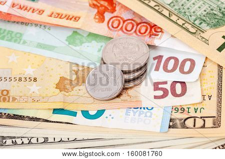Russian rubles coins over different currency banknotes close up