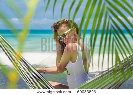 Woman in a hammock on a sandy beach in the shade of palm trees