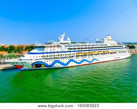 Venice, Italy - June 06, 2015: Cruise liner AIDA Vita docked at the port of Venice, Italy on a background of the roofs on June 06, 2015