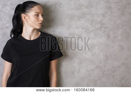 Portrait of attractive caucasian girl in black shirt on textured concrete background with copy space