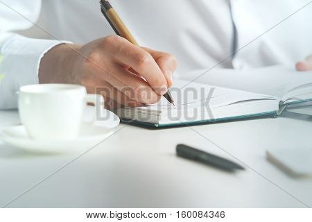 Close up of man at office desktop writing in organizer. Business concept
