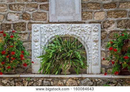 Bas-relief with floral ornament and flowers in pots adorns the courtyard of the Cana Greek Orthodox Wedding Church in Cana of Galilee Kfar Kana Israel.