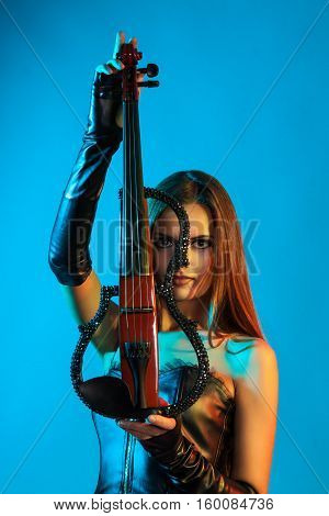 Young female violinist playing violin. The girl on a blue background