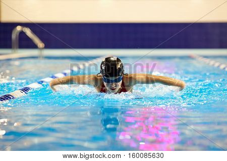 Swimmer girl teenager in the pool swims butterfly inside