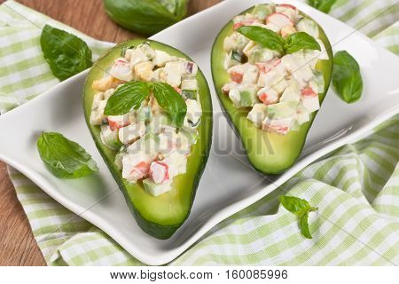 Avocado stuffed with crab cucumber egg red onion and sauce mayonnaise on white plate