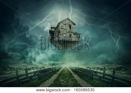 Ghost house ripped from the ground flying above a country road in a stormy day with lightnings in the sky.