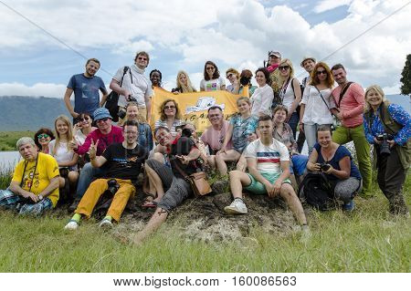 AFRICA, TANZANIA, MAY, 10, 2016 - Large and fun group of travellers on Africa posing for photos on the memory together in Ngorongoro Crater, national park Tanzania.