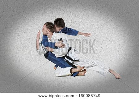 The two judokas fighters fighting men on gray background
