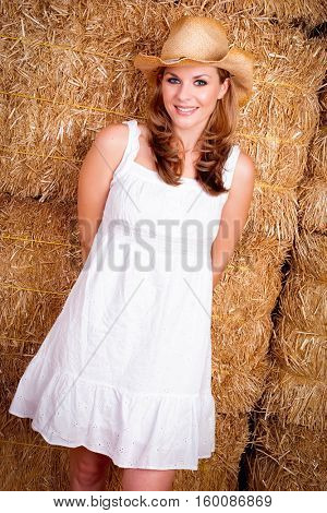 Beautiful smiling country girl in hay