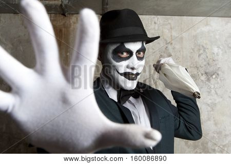 Scary evil clown wearing a bowler hat on wall background