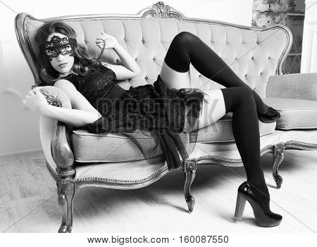 Sexy young woman lying on the sofa in black stockings and a mask. Sensual Woman in lace mask and stockings posing on vintage couch. Monochrome