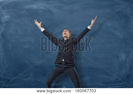 A businessman standing with splayed arms and shouting on the blue blackboard background. Bright and vivid emotions. The best in his field. Business development and the way to success. With great enthusiasm poster