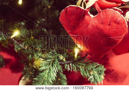 Christmas background - a toy on the Christmas tree on the background of garlands in the form of hearts