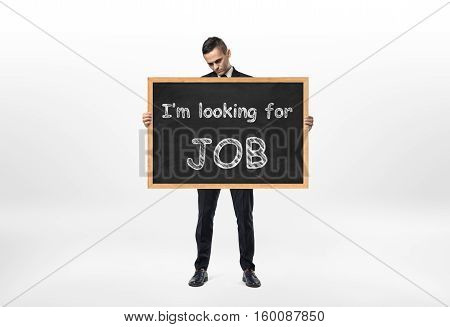 Businessman standing and holding blackboard with words 'I'm looking for job' written on it. Issues of small business. Freelance. Economic crises. Vacancy search.