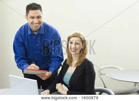Workers Smile Near Desk