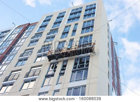 Repair and restoration of a facade of a high building. Workers making repairs on a facade
