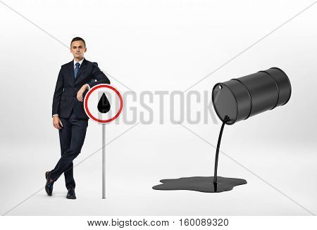 A businessman leaning on the road sign with the oil drop depicted on it, and oil pouring out of the black barrel, isolated on the white background. Oil and petroleum products. Black gold. Resource extraction.
