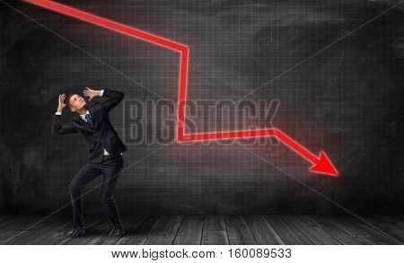 A small frightened businessman under a huge red kinked arrow pointing down on a dark plaid background. Business falling down. Negative trend. Crisis impact.