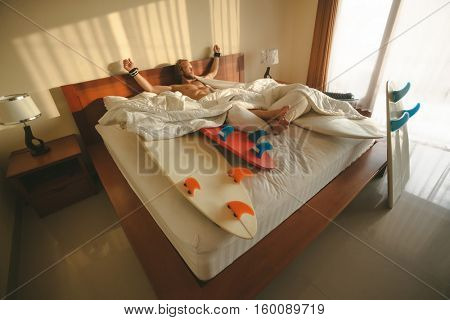 Surfer wakes up with his boards in bed