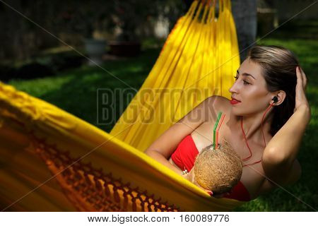 Attractive young woman laying down and relaxing on a white hammock while on vacation in a tropical garden.