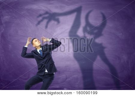 Shadow of devil trying to catch the frightened businessman. Temptation of money. Trapped by greedy desires. Personal demons. Business issues.