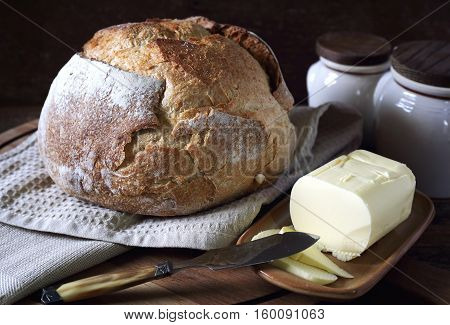 French sourdough bread and butter on dark wooden chopping board