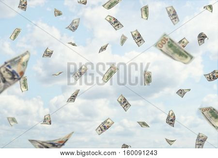 Lots of hundred dollars banknotes falling from the blue cloudy sky. Sudden changes in income. Make profits. Business development. Rise in profitability.